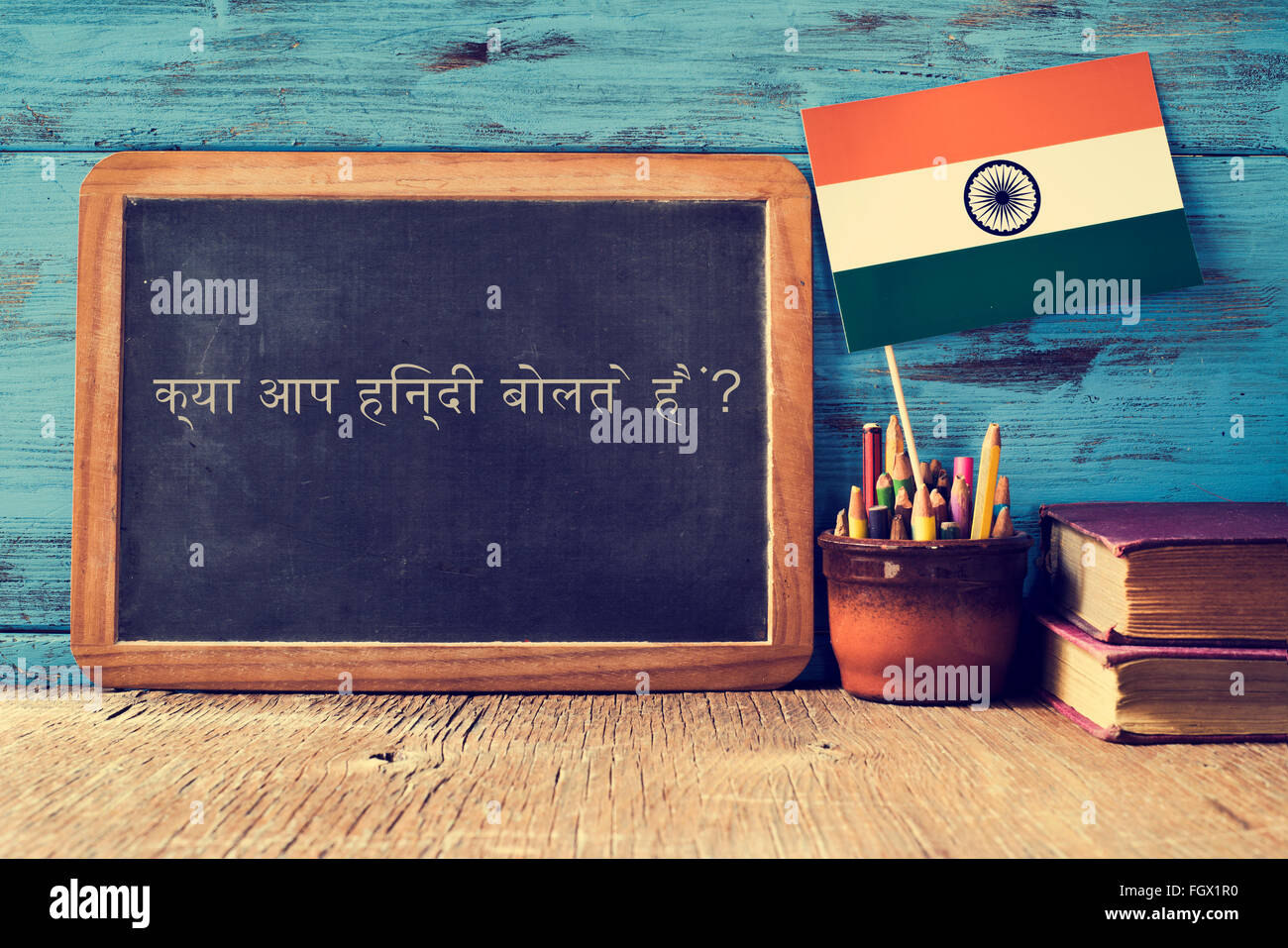 a chalkboard with the question do you speak hindi? written in hindi, a pot with pencils, some books and the flag - Stock Image
