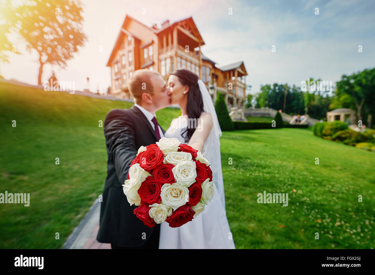 European bride and groom kissing in the park near house - Stock Image