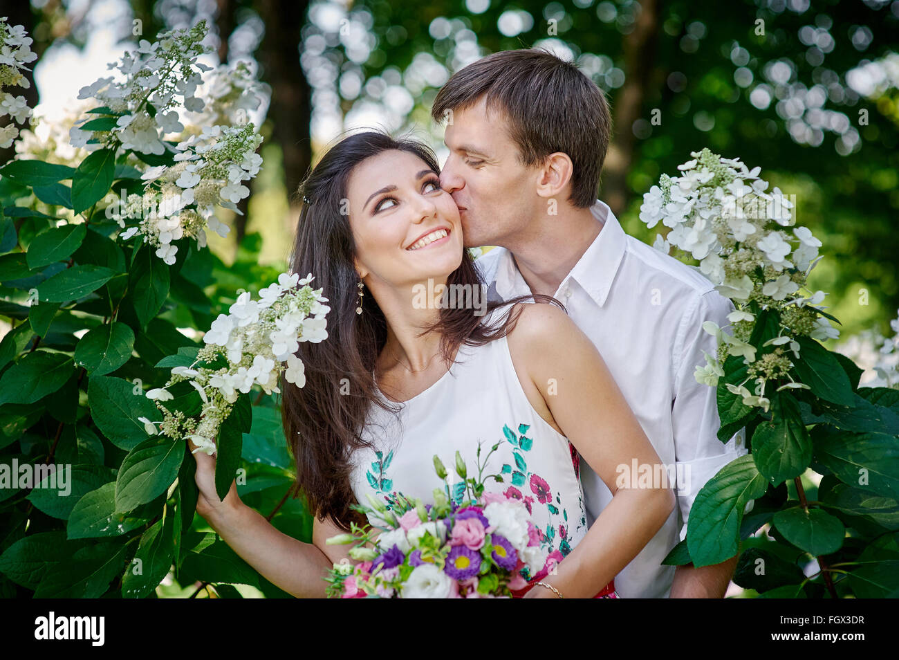 elegant groom with his happy bride kisses in the park - Stock Image