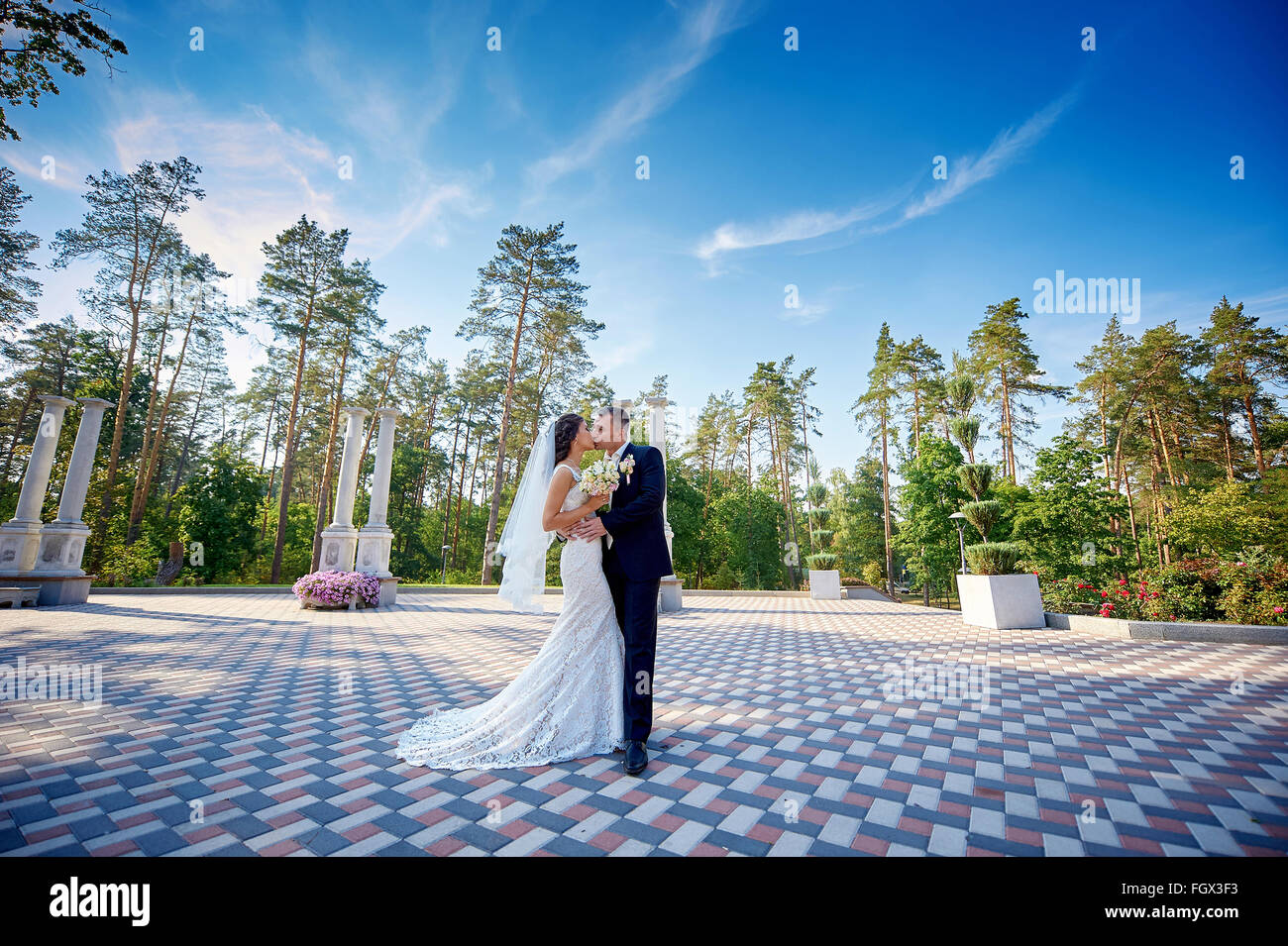 elegant stylish groom with his happy gorgeous bride kisses in the park - Stock Image