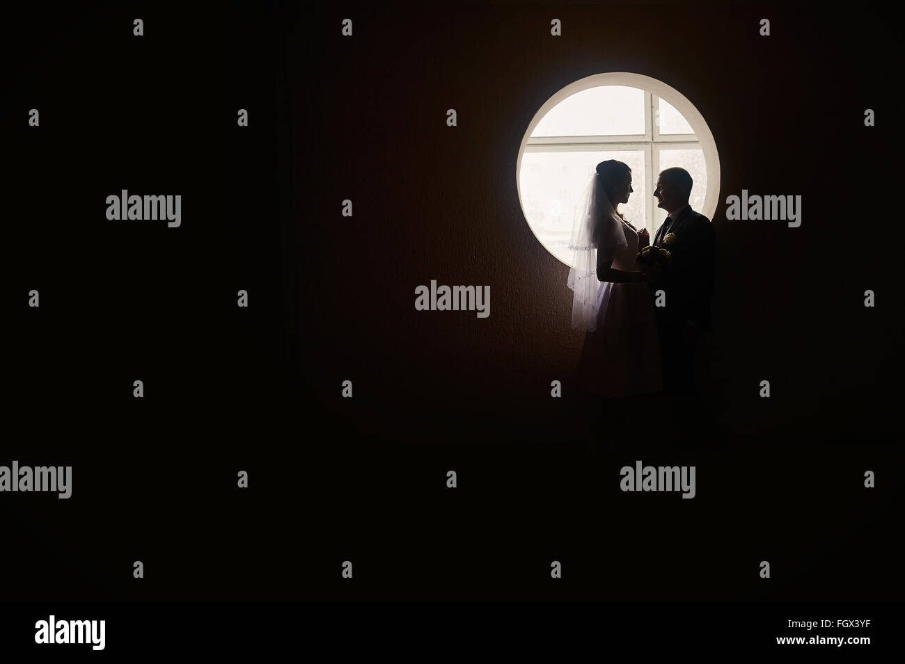 silhouette of a bride and groom on the background of the window - Stock Image