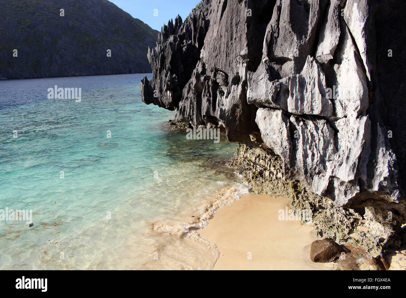 Transparent blue-green waters, golden sands and limestone in Matinloc island, in the archipelago of El Nido - Stock Image