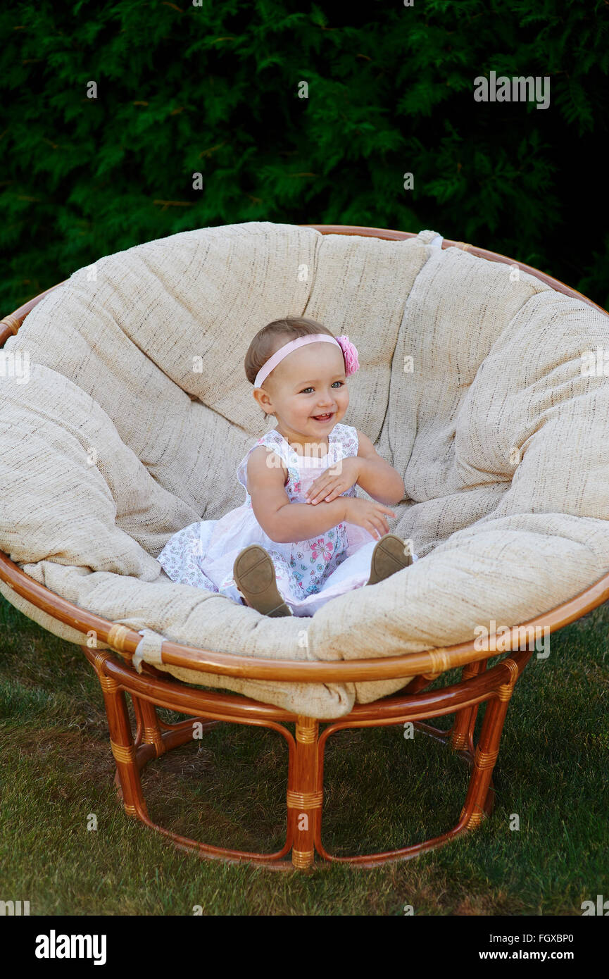 Little baby girl poses on a white chair.  She is smiling happily Stock Photo