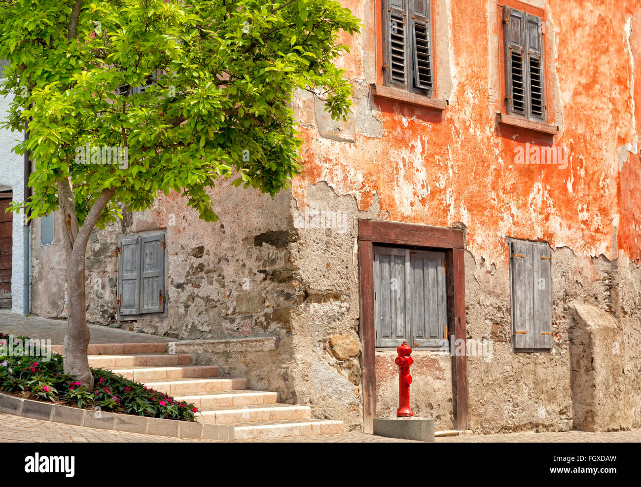 Old red historic corner house with aged walls and shutter windows, on cobbled street, with red water hydrant and - Stock Image