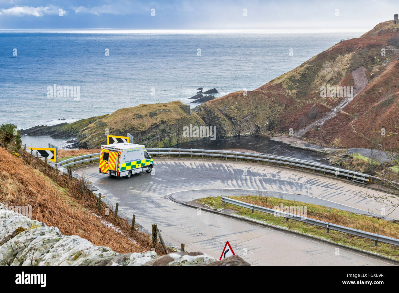 BERRIEDALE BRAES A SCOTTISH AMBULANCE NEGOTIATES A BEND ON THE A9 IN WINTER WEATHER WITH SLEET - Stock Image