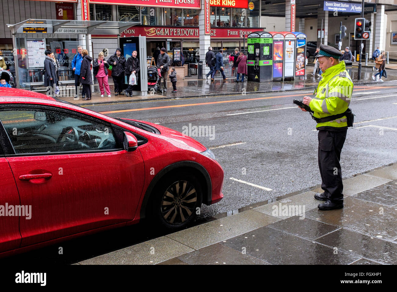 Traffic warden issuing a parking ticket to a car parked illegally in Glasgow city centre, Scotland, UK - Stock Image