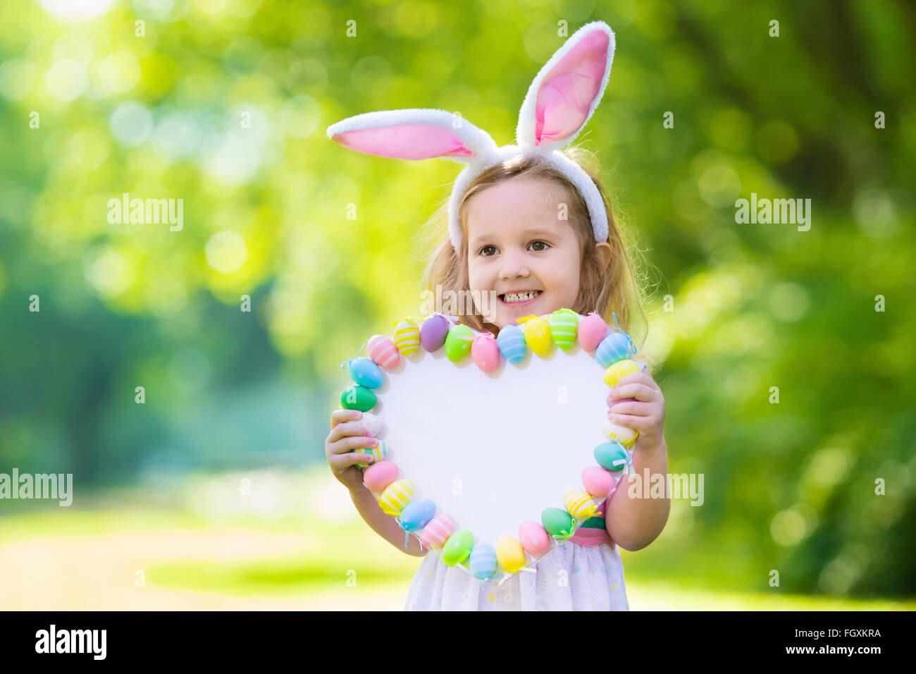 Little Girl Having Fun On Easter Egg Hunt Kids In Bunny Ears And