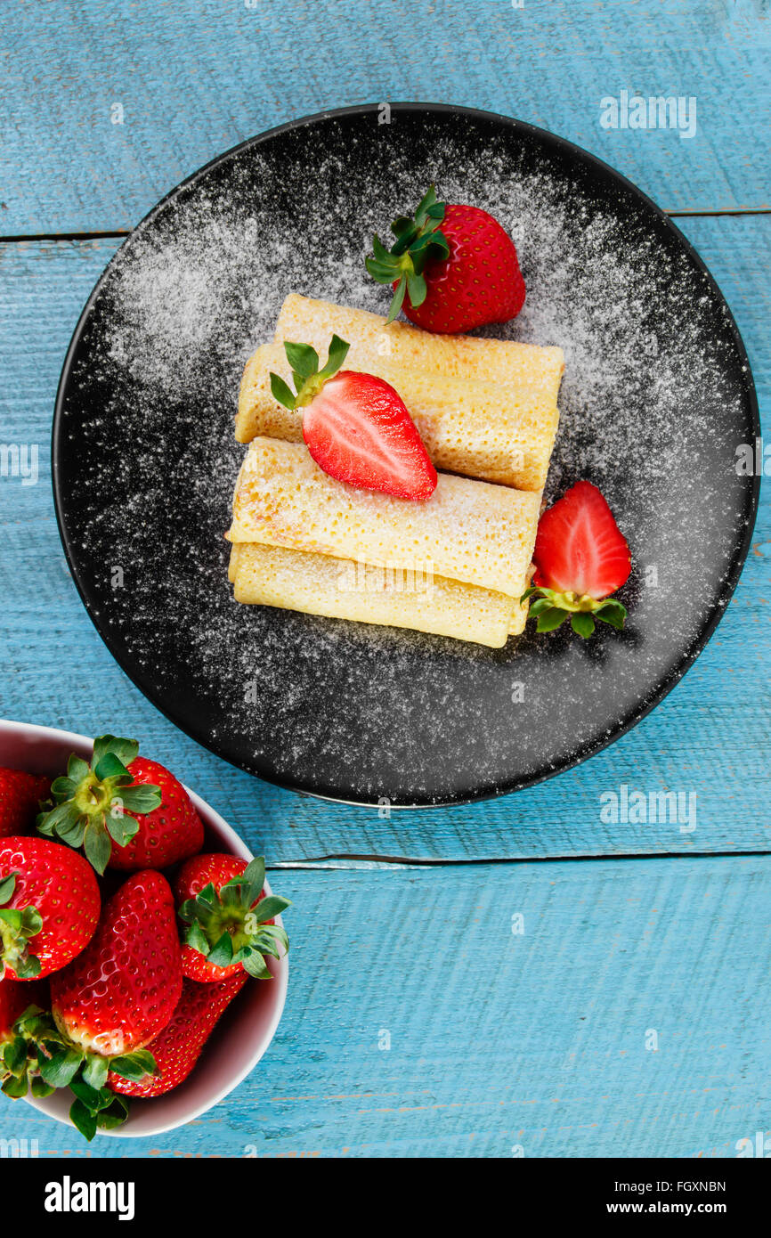 rolled pancakes with strawberries breakfast - Stock Image