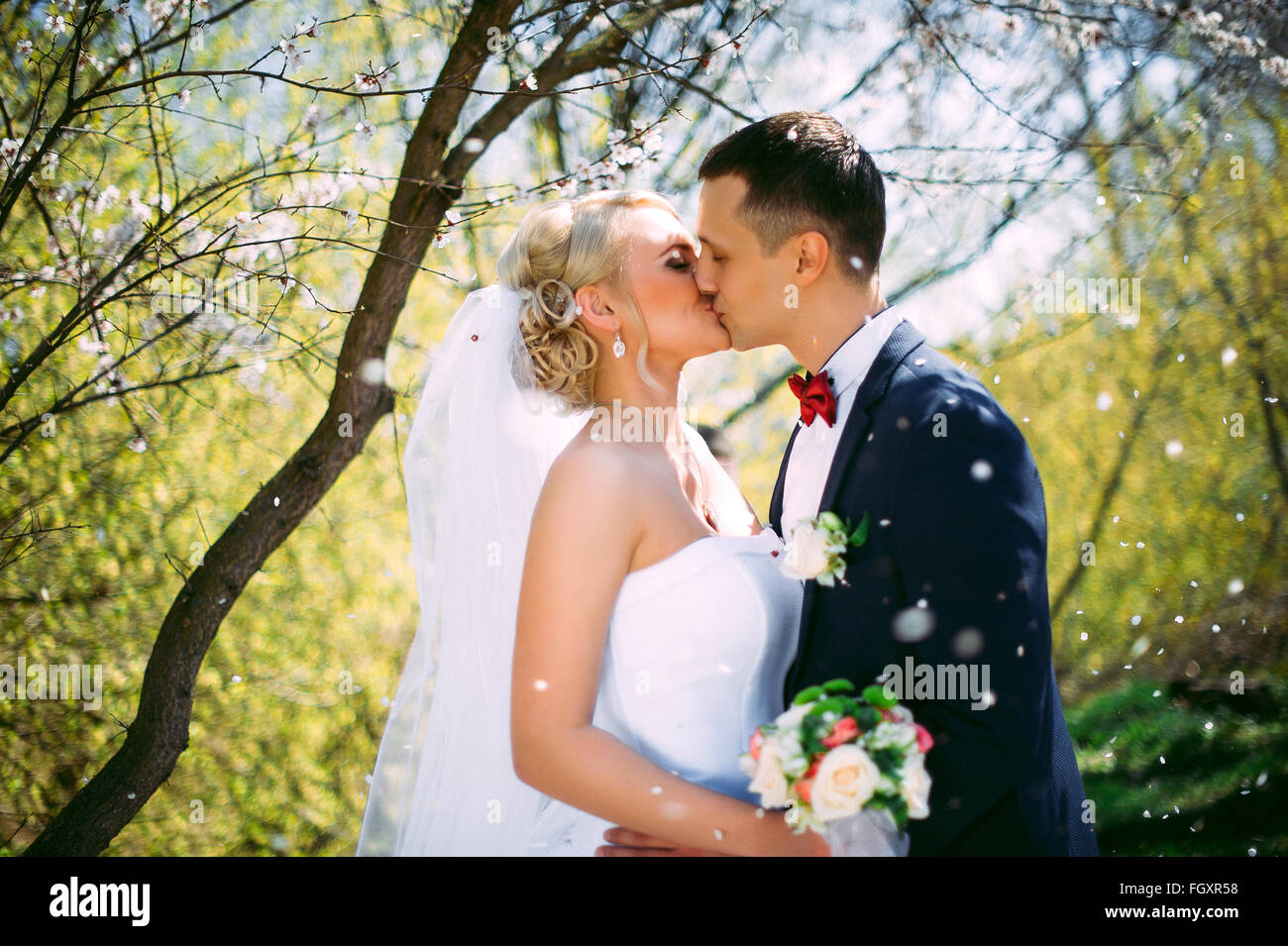 Kissing wedding couple in spring nature close-up portrait. Kissing wedding couple in spring nature close-up portrait - Stock Image