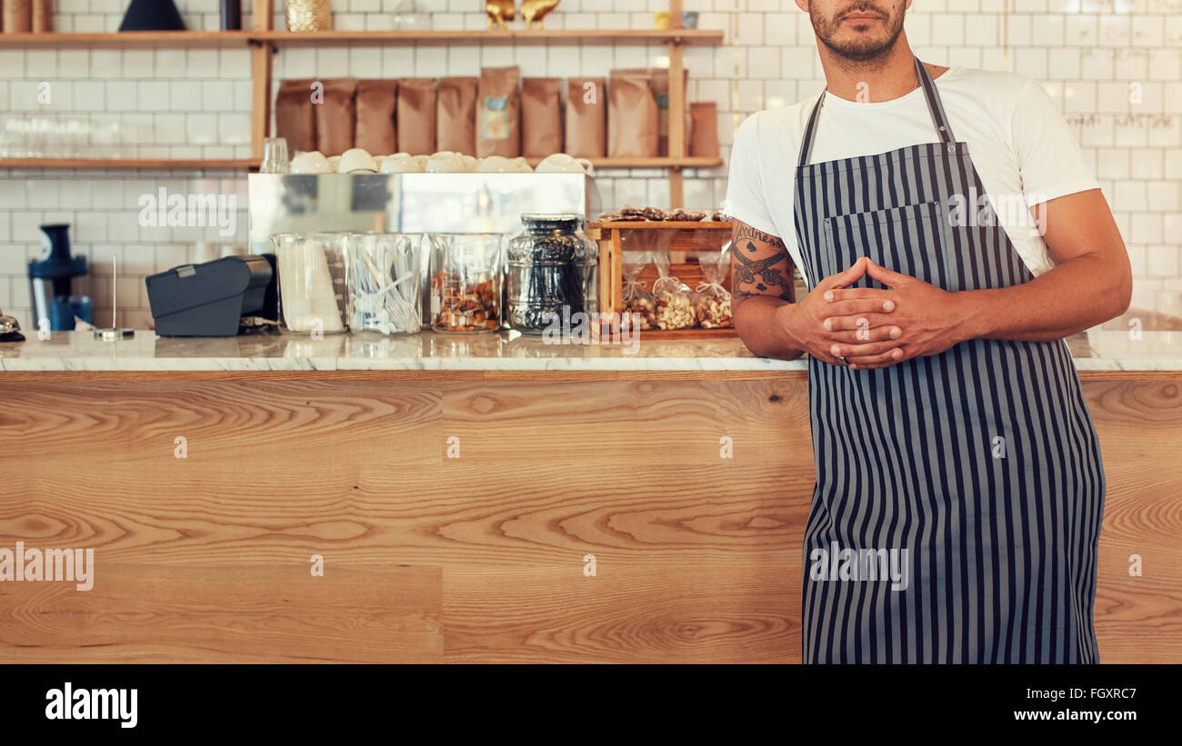 Cropped shot young man standing at a coffee shop counter wearing an apron. He is leaning to the cafe counter with - Stock Image
