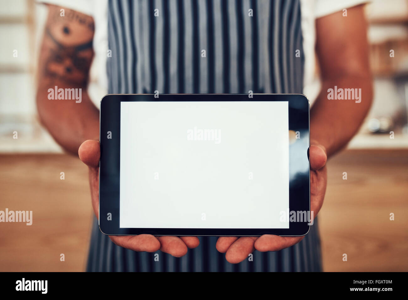 Close up portrait of a man wearing an apron holding a digital tablet with a blank white screen. Waiter holding a - Stock Image