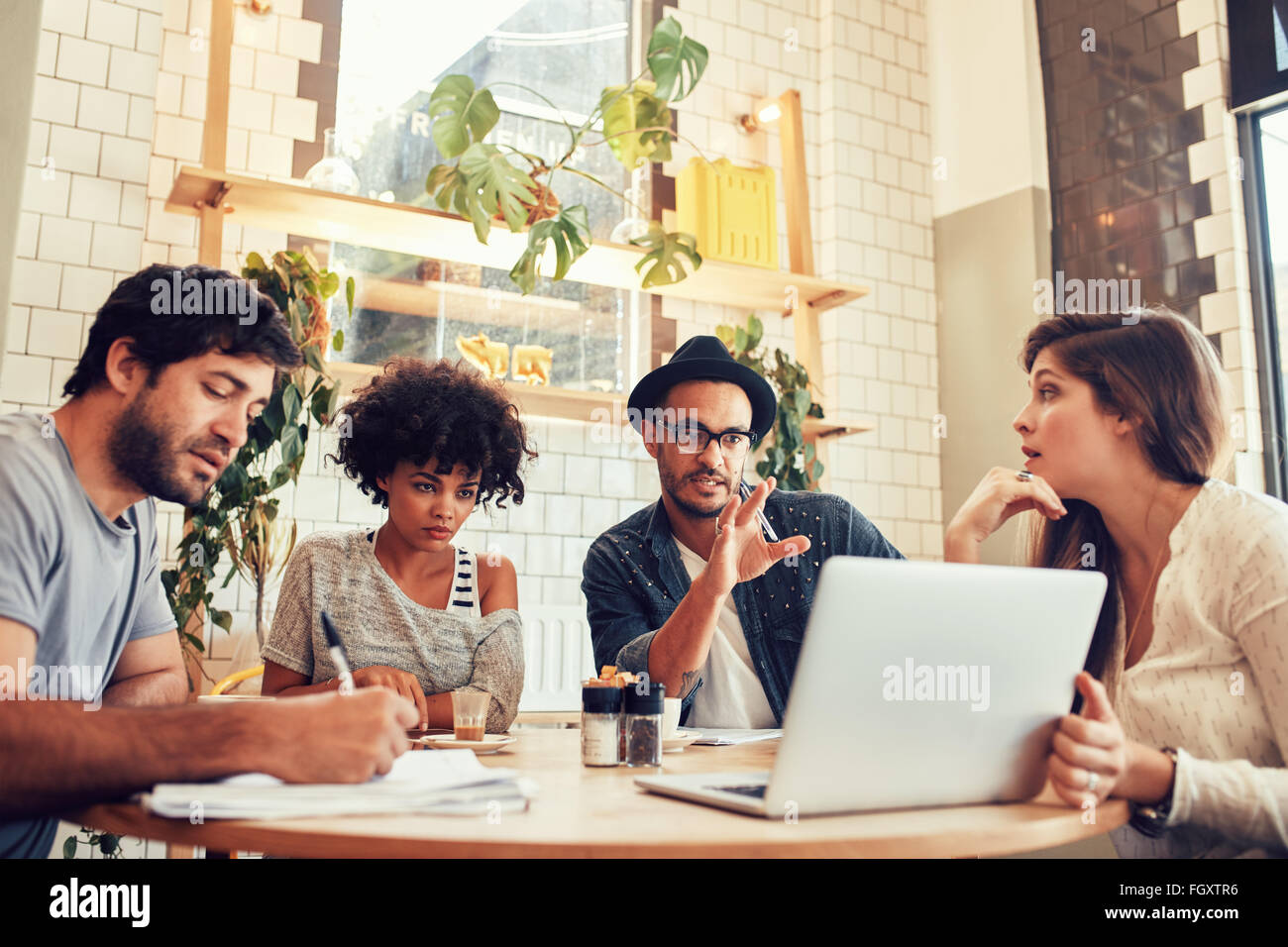 Portrait of creative business team sitting at a coffee shop with laptop. Young man discussing new business ideas - Stock Image