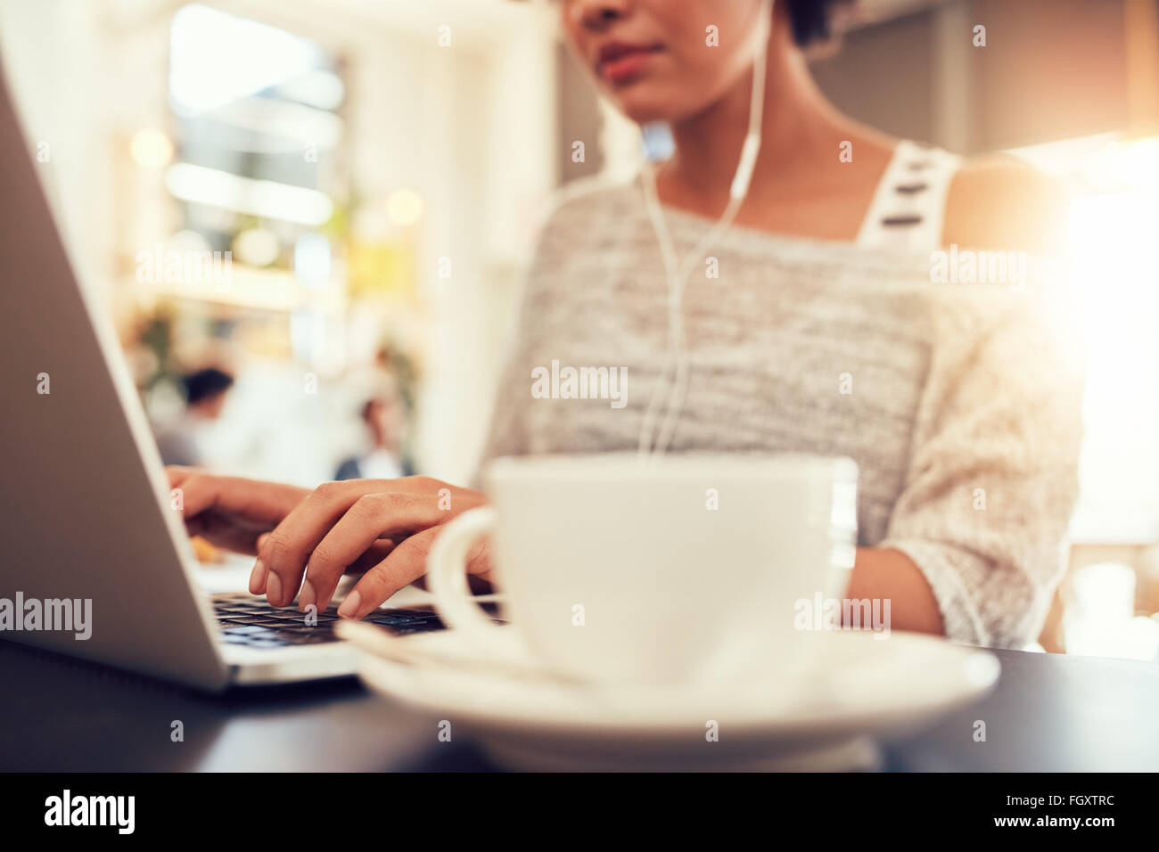 Woman sitting at a coffee shop working on laptop, with focus on hands typing on keyboard. - Stock Image