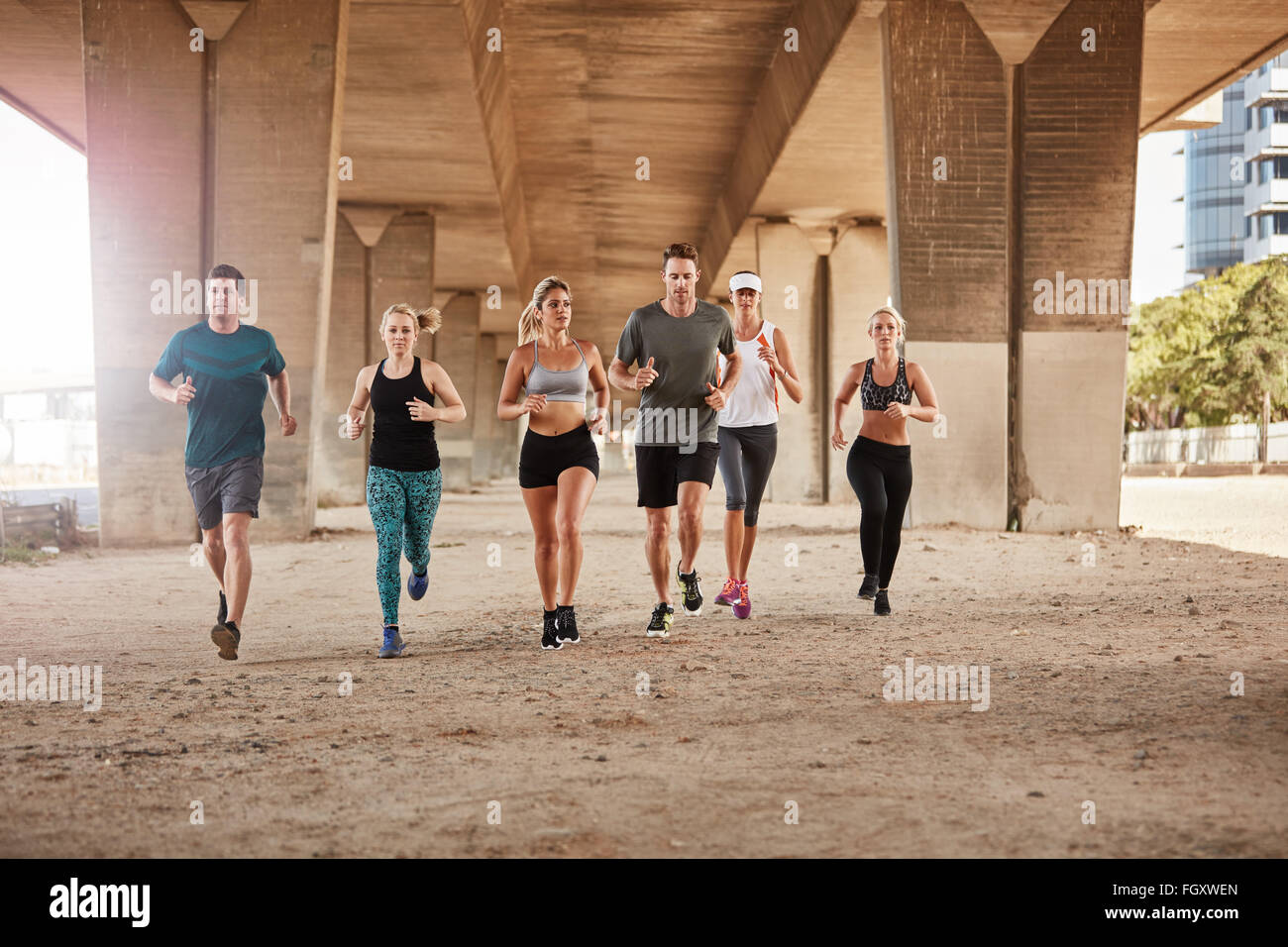 Portrait of group of healthy young people running together in city. Running club members training together in morning - Stock Image