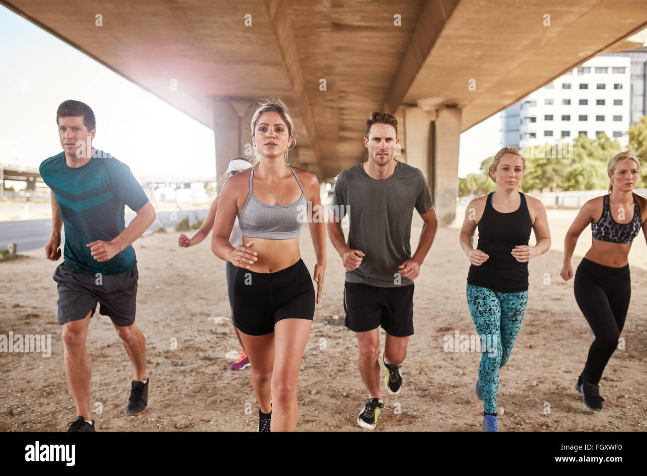 Determined group of athletes running. Runners in sportswear training together in the city. - Stock Image