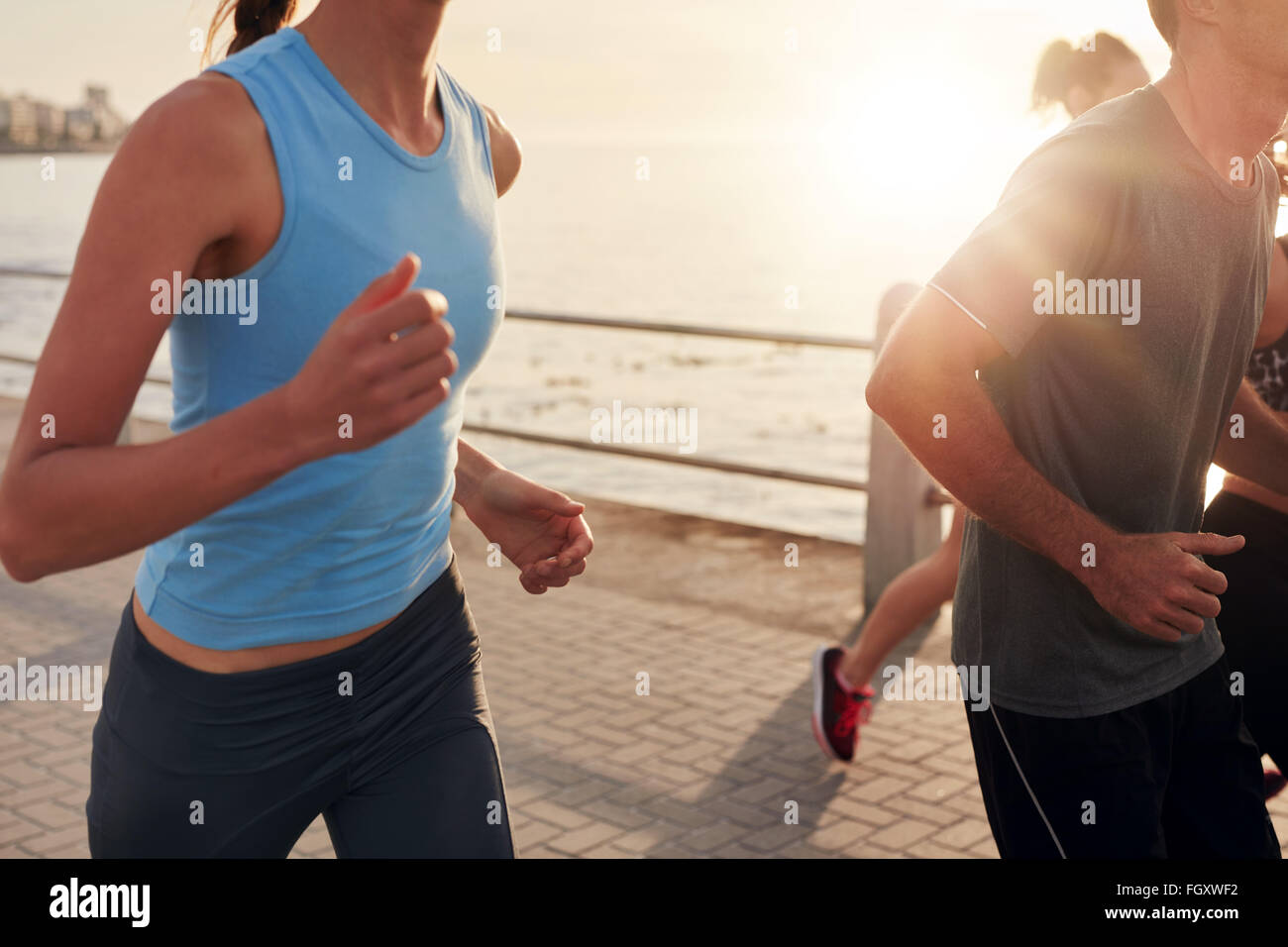 Cropped shot of young people running along seaside at sunset. Closeup image of group of runners working out on a - Stock Image