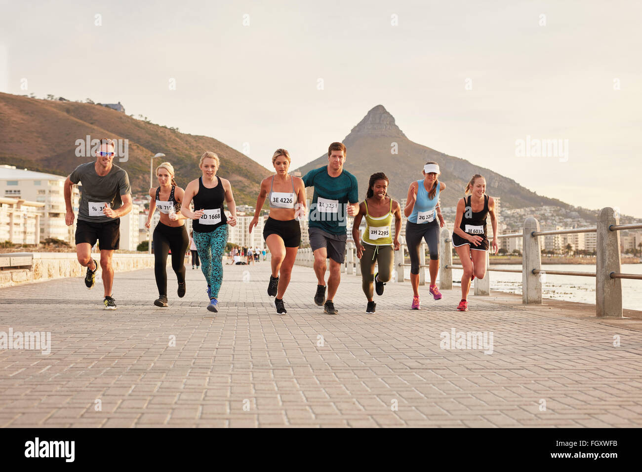 Diverse group of young people running along a seaside promenade. Fit young runners training outdoors by the seaside. - Stock Image