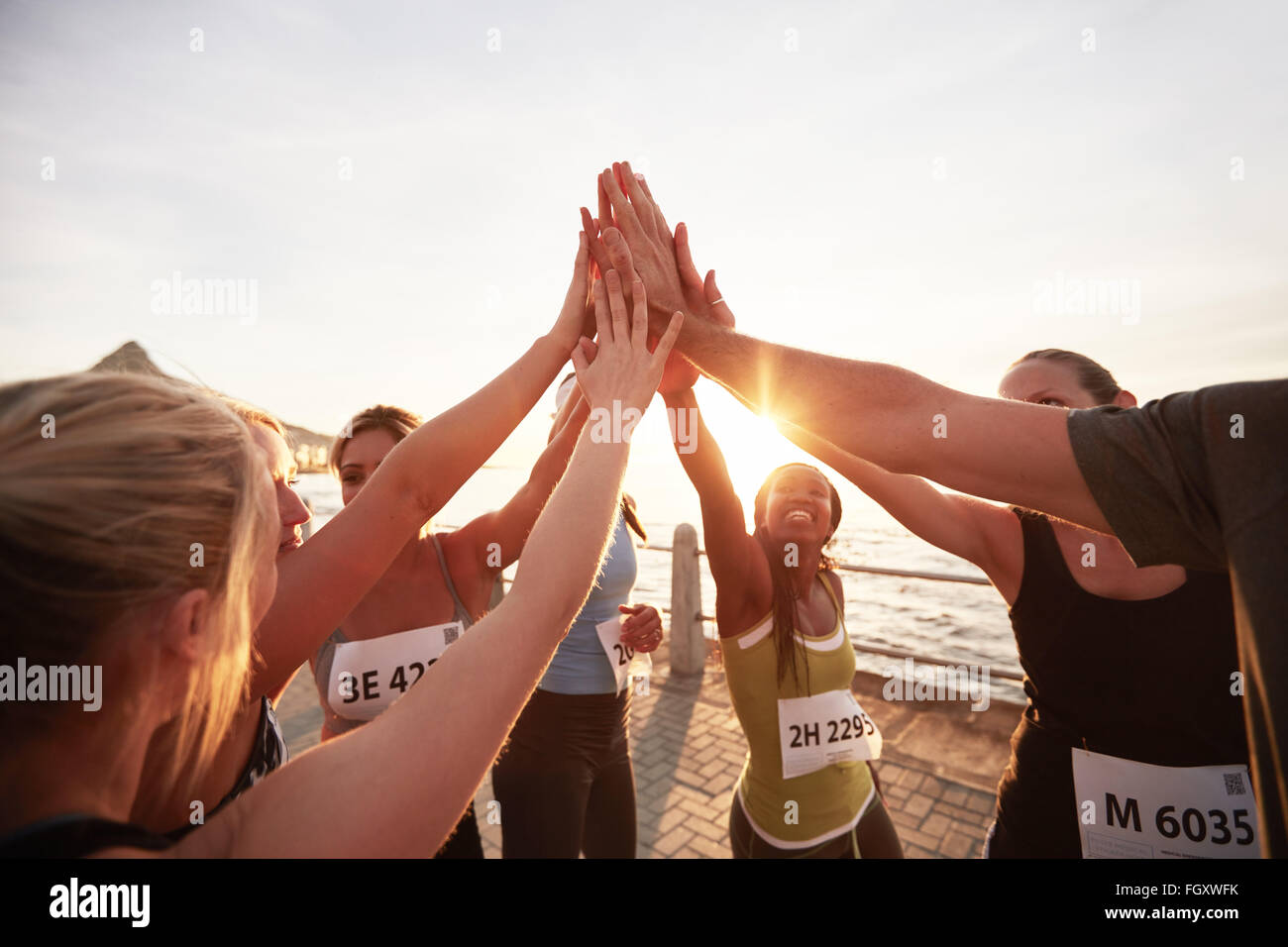 Athletic team with their hands stacked together celebrating success. Marathon runners giving high five. - Stock Image