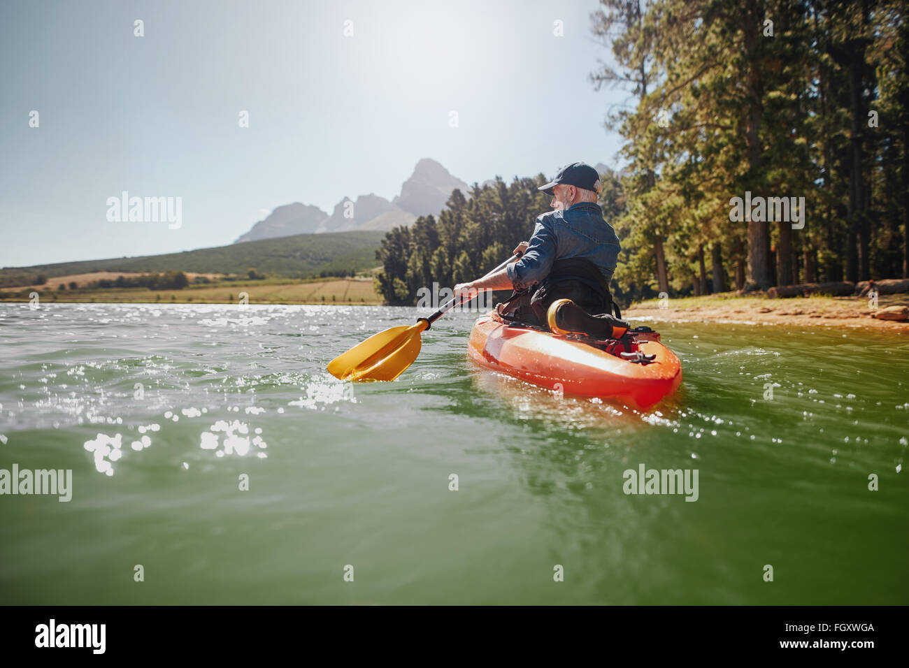 Rear view of a mature man canoeing in a lake. Senior man paddling kayak on a summer day. - Stock Image