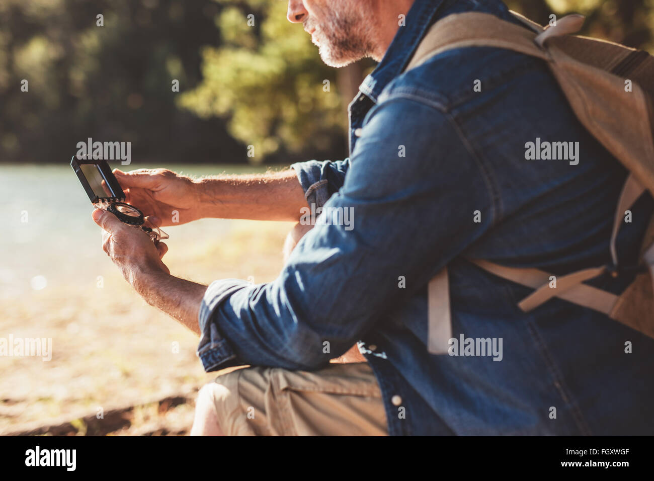 Cropped portrait of mature man sitting at a lake using a compass for navigation. Hiker man searching direction with - Stock Image