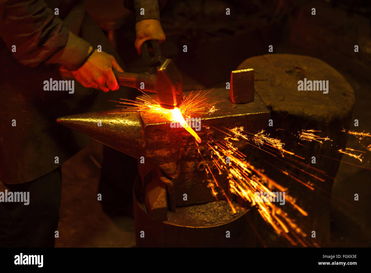 Blacksmith forfing hot iron - Stock Image