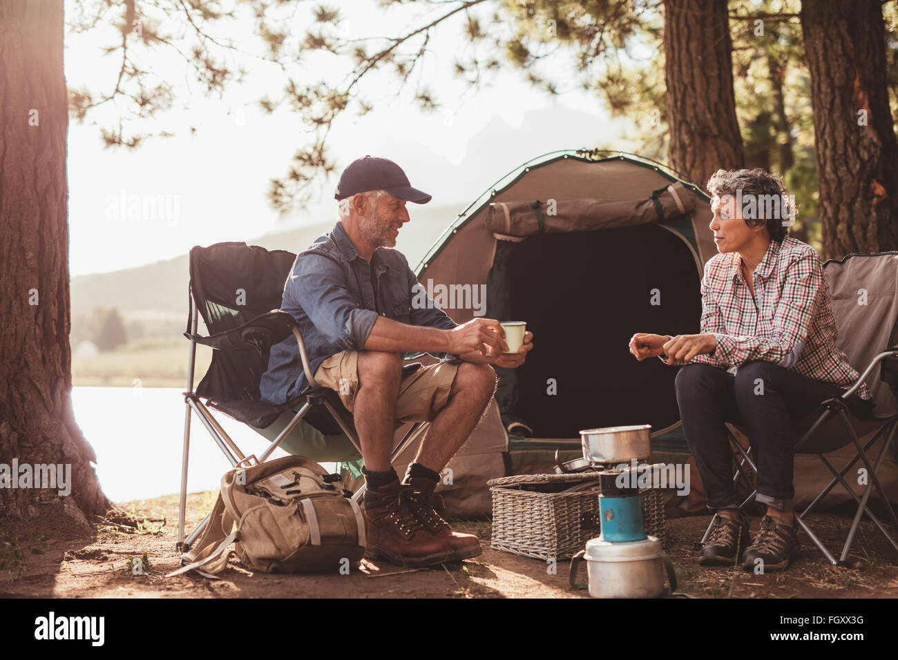 Portrait of happy mature campers enjoying coffee by the lake. Mature couple relaxing at their campsite. Stock Photo