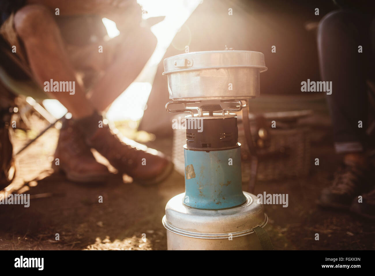 Close up portrait of a camp stove with couple sitting in background. - Stock Image