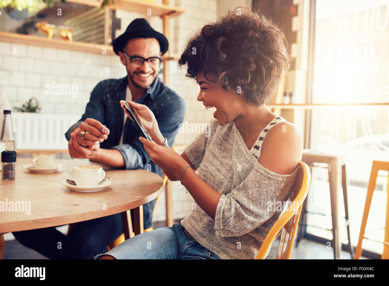 Portrait of smiling young woman at a cafe table looking at digital tablet with a friend sitting by. - Stock Image