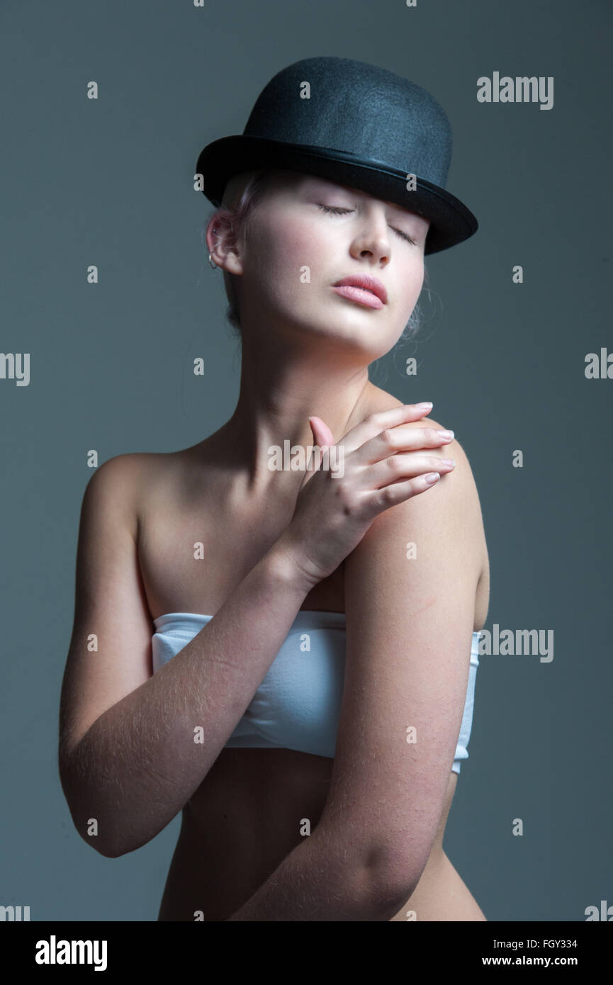 97fa901ba7a young lady posing in a black bowler hat with hands touching her body ...