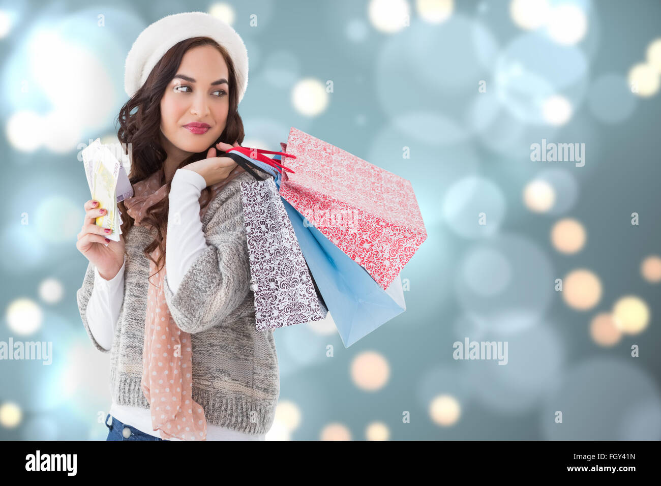 Composite image of brunette holding cash and shopping bags - Stock Image