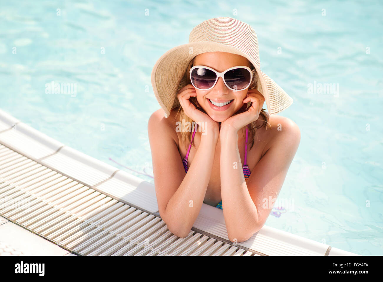 Woman with sunglasses and hat in swimming pool, water Stock Photo