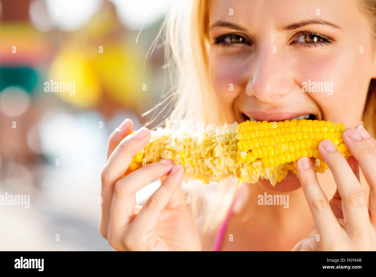 Woman in bikini eating corn. Summer and heat. - Stock Image