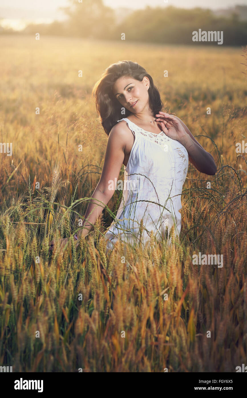 Portrait of a beautiful woman in a field. Summer sunset light - Stock Image