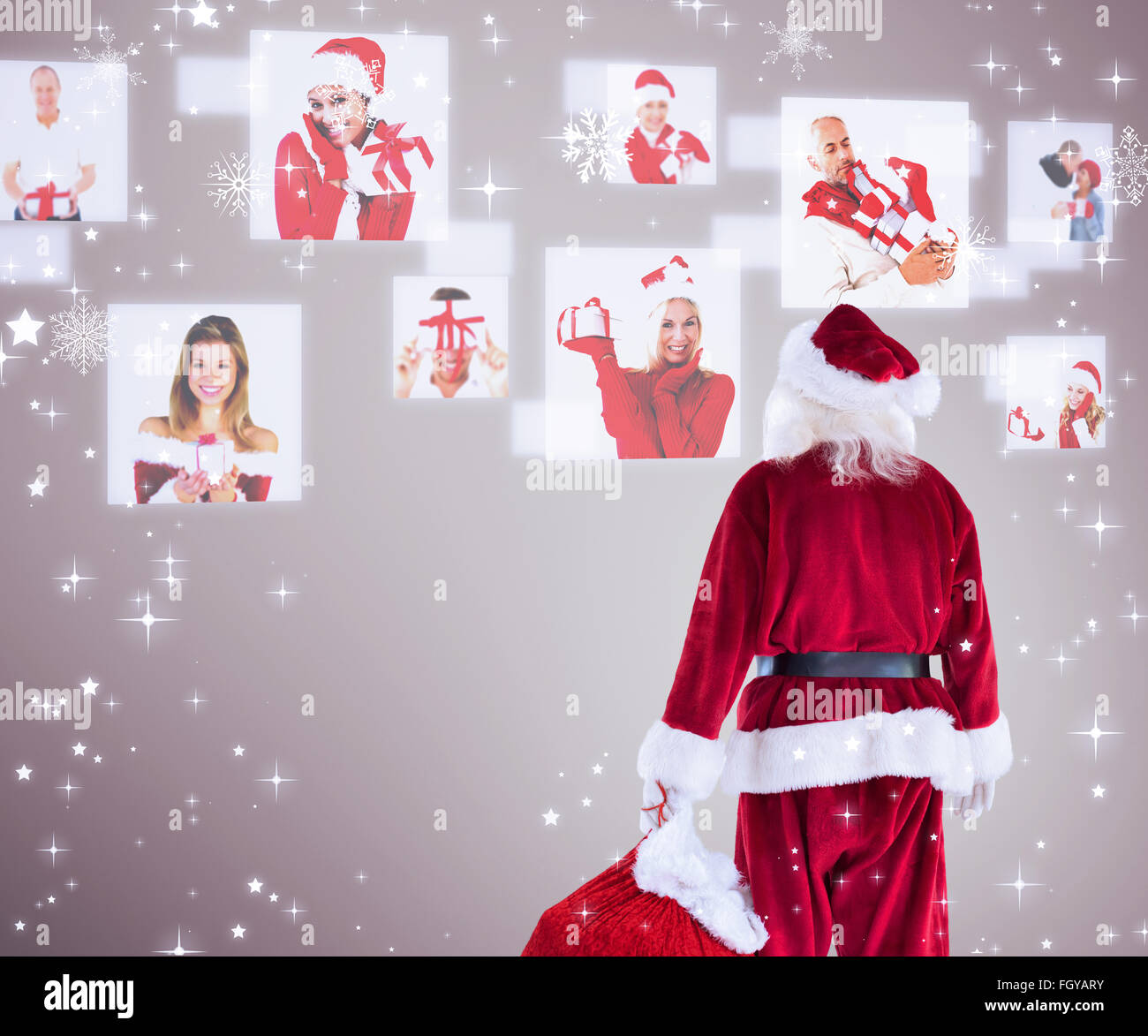 Composite image of santa carrying sack of gifts - Stock Image