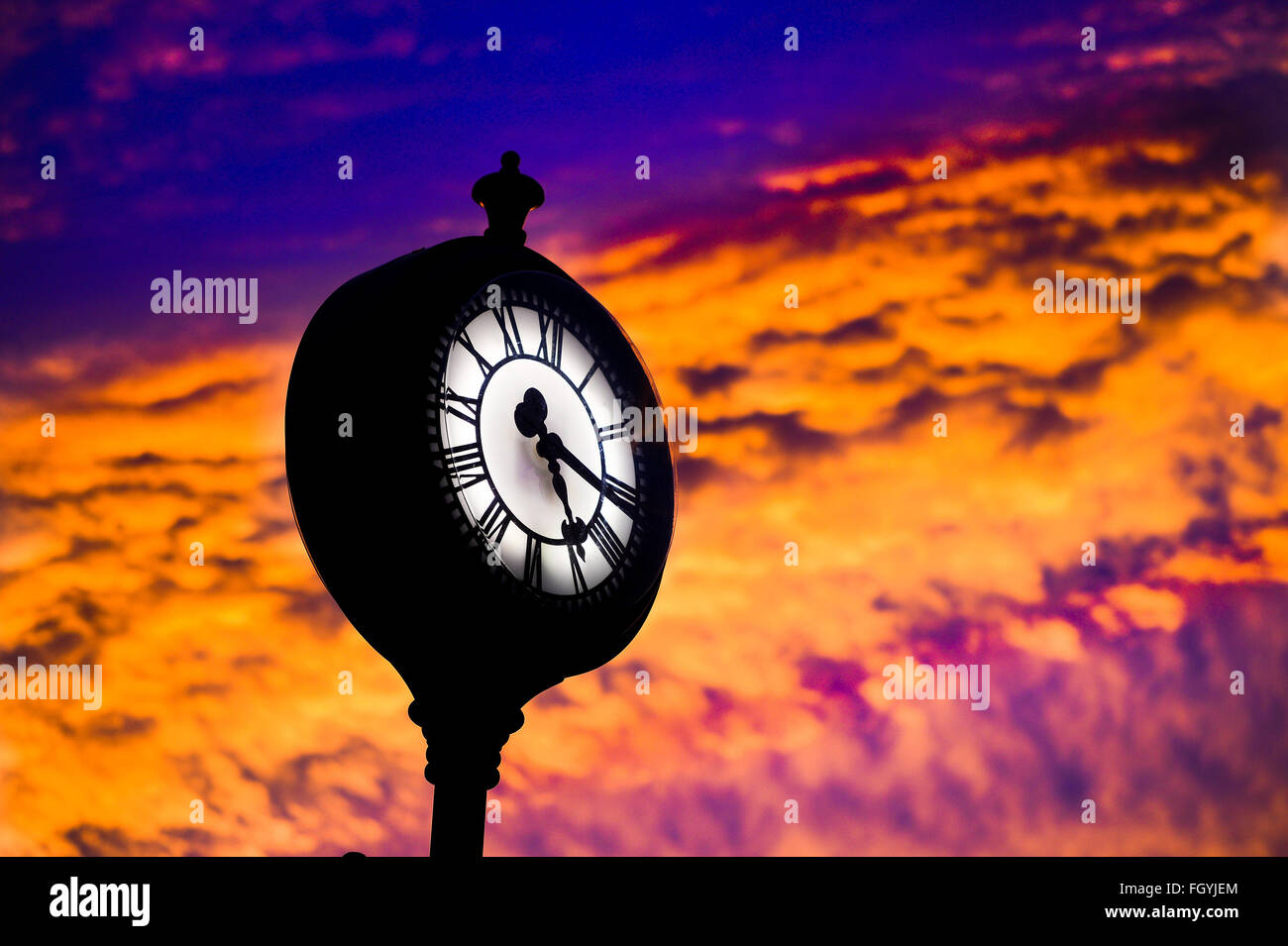 Public clock against a strong sunset showing the time on a roman numeral face of quarter past five. - Stock Image