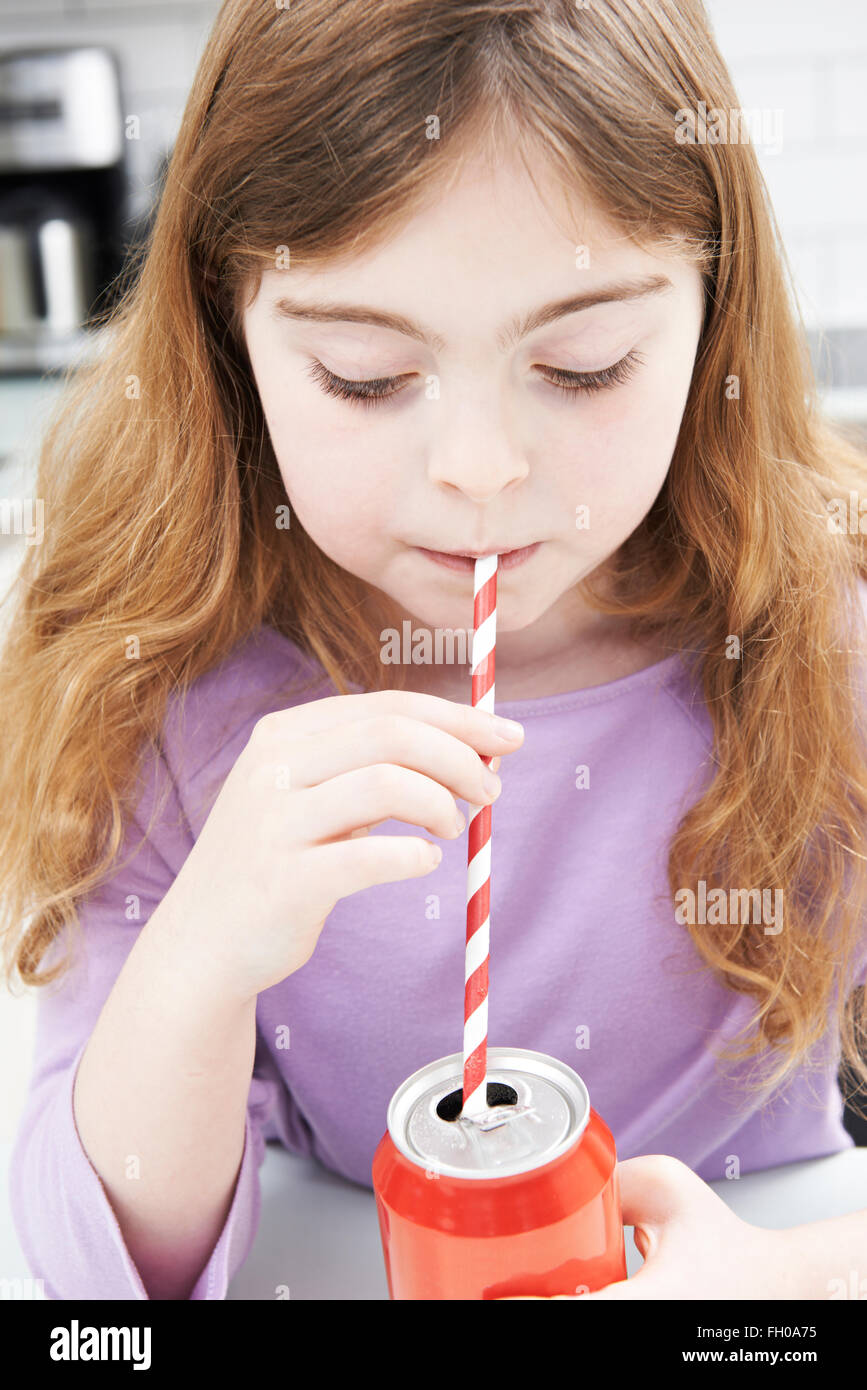 Young Girl Drinking Can Of Soda Through Straw - Stock Image