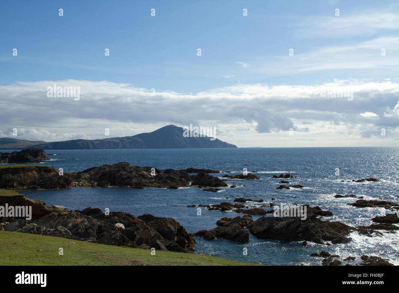 A rock foreshore on Achill island, Co. Mayo in the west of Ireland with the Atlantic and mountain in the background - Stock Image