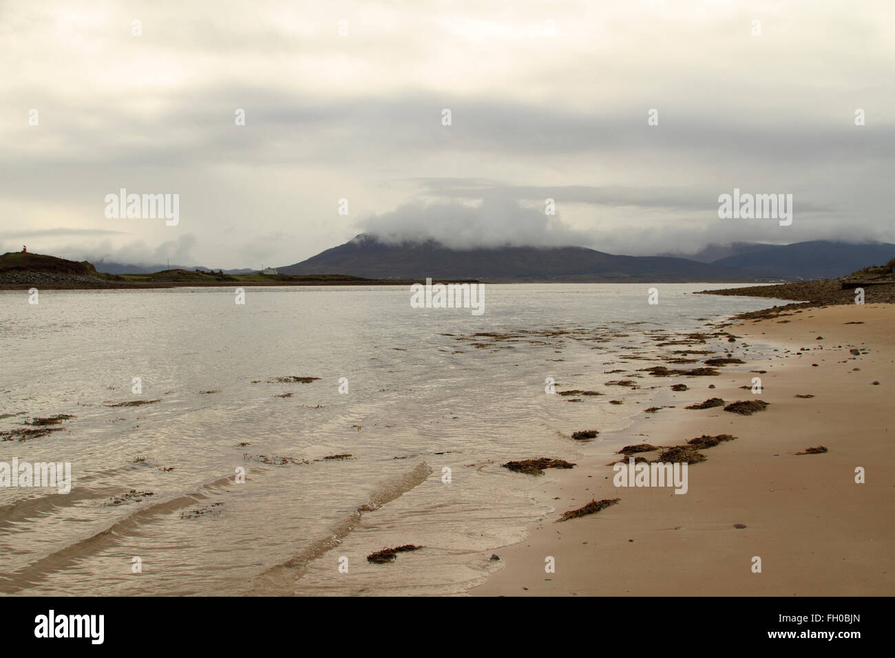 A deserted strand on Achill Island, Co. Mayo, West of Ireland with a mist covered mountain in the background - Stock Image