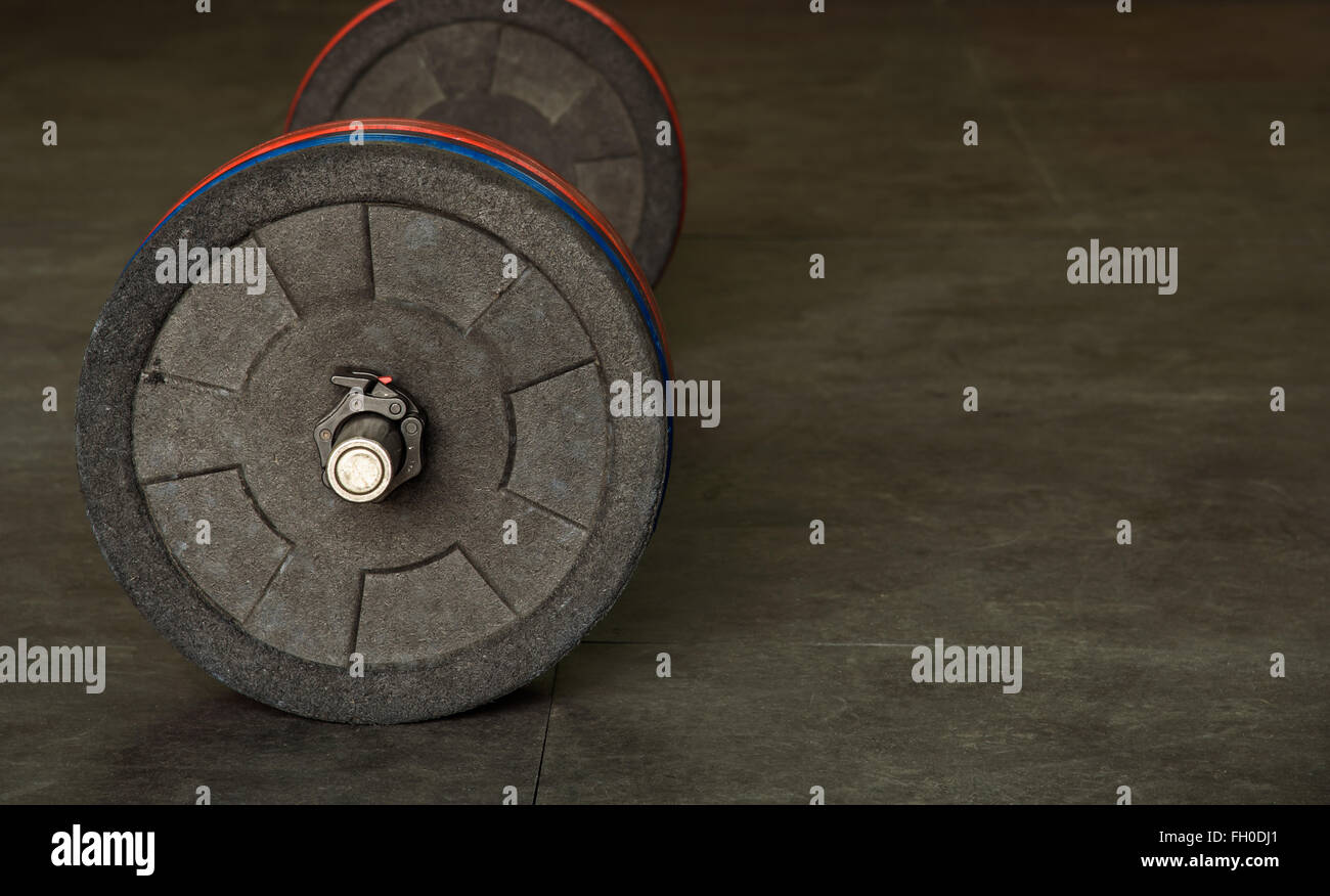 Barbell with black, blue, and red weight plates - Stock Image