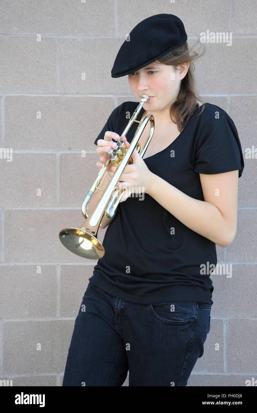 Female trumpet player blowing. - Stock Image