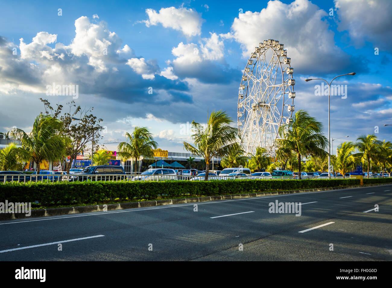 Ferris wheel and Seaside Boulevard, in Pasay, Metro Manila, The Philippines. - Stock Image