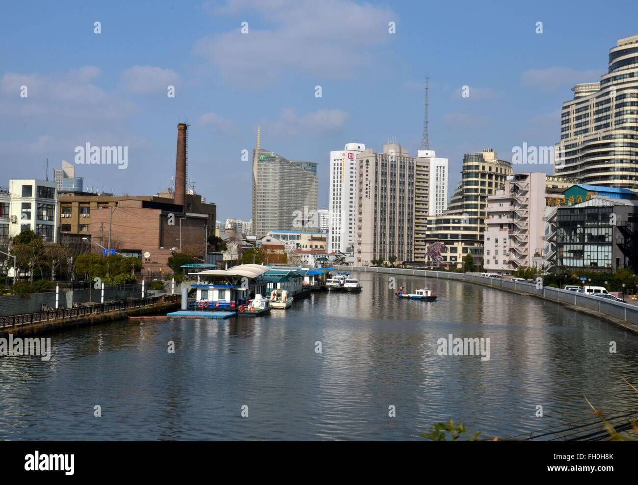 River canal with utility boat chimney and tall buildings Holiday Inn hotel Shanghai China - Stock Image