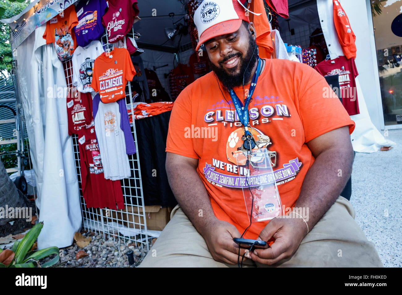Miami Beach Florida Ocean Drive New Year's Eve Black man texting smartphone sidewalk vendor sale display souvenirs - Stock Image