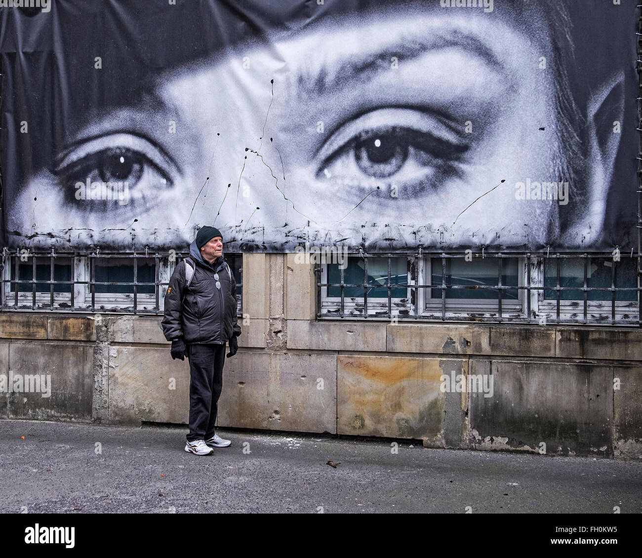 Elderly man standing outside Berlin Rath Factory exterior with B & W photograph of giant eyes, Mitte Berlin - Stock Image
