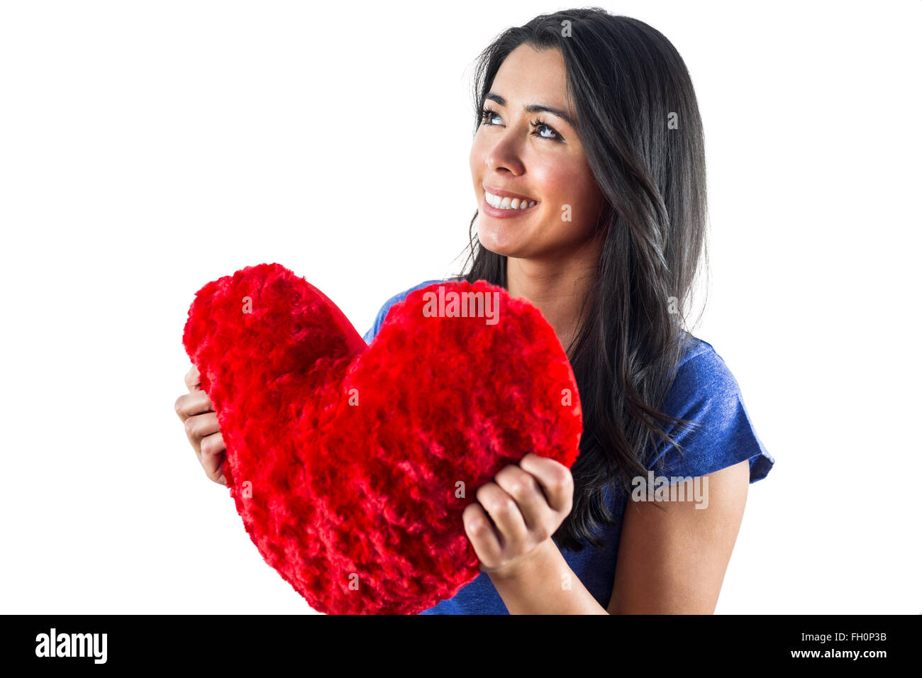 Smiling woman holding a heart shaped pillow - Stock Image