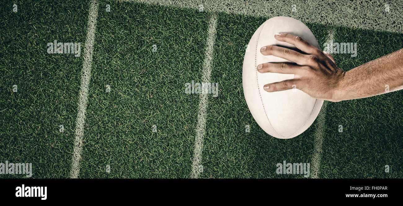 Composite image of cropped image of sports player holding ball - Stock Image