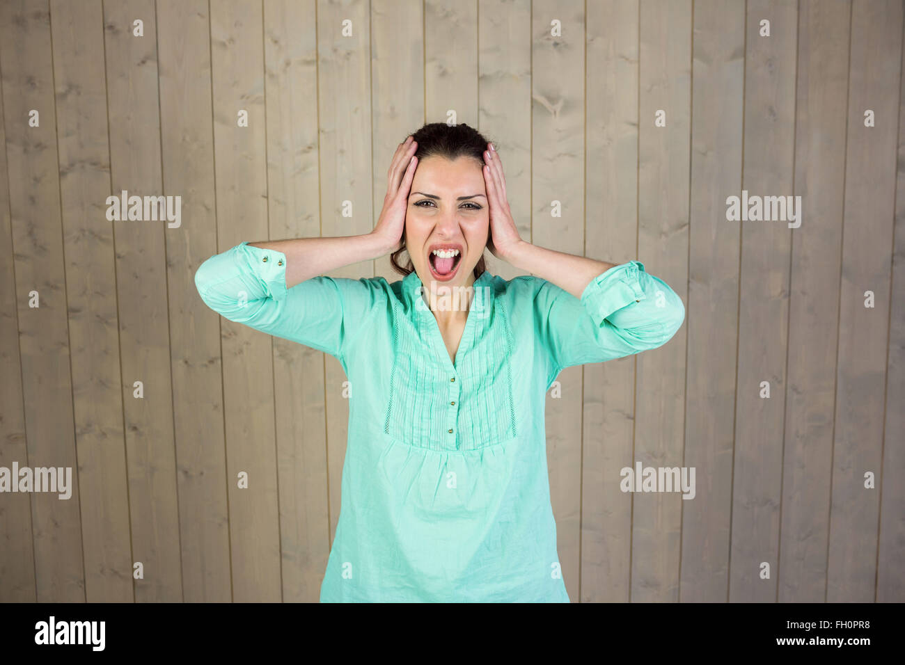 Portrait of woman screaming with head in hands - Stock Image