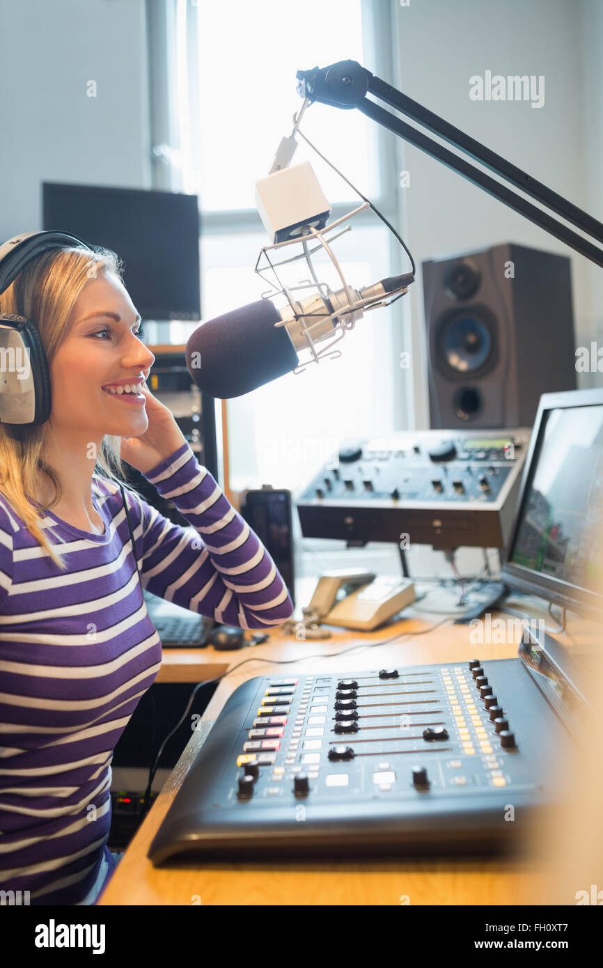 Happy female radio host broadcasting through microphone - Stock Image