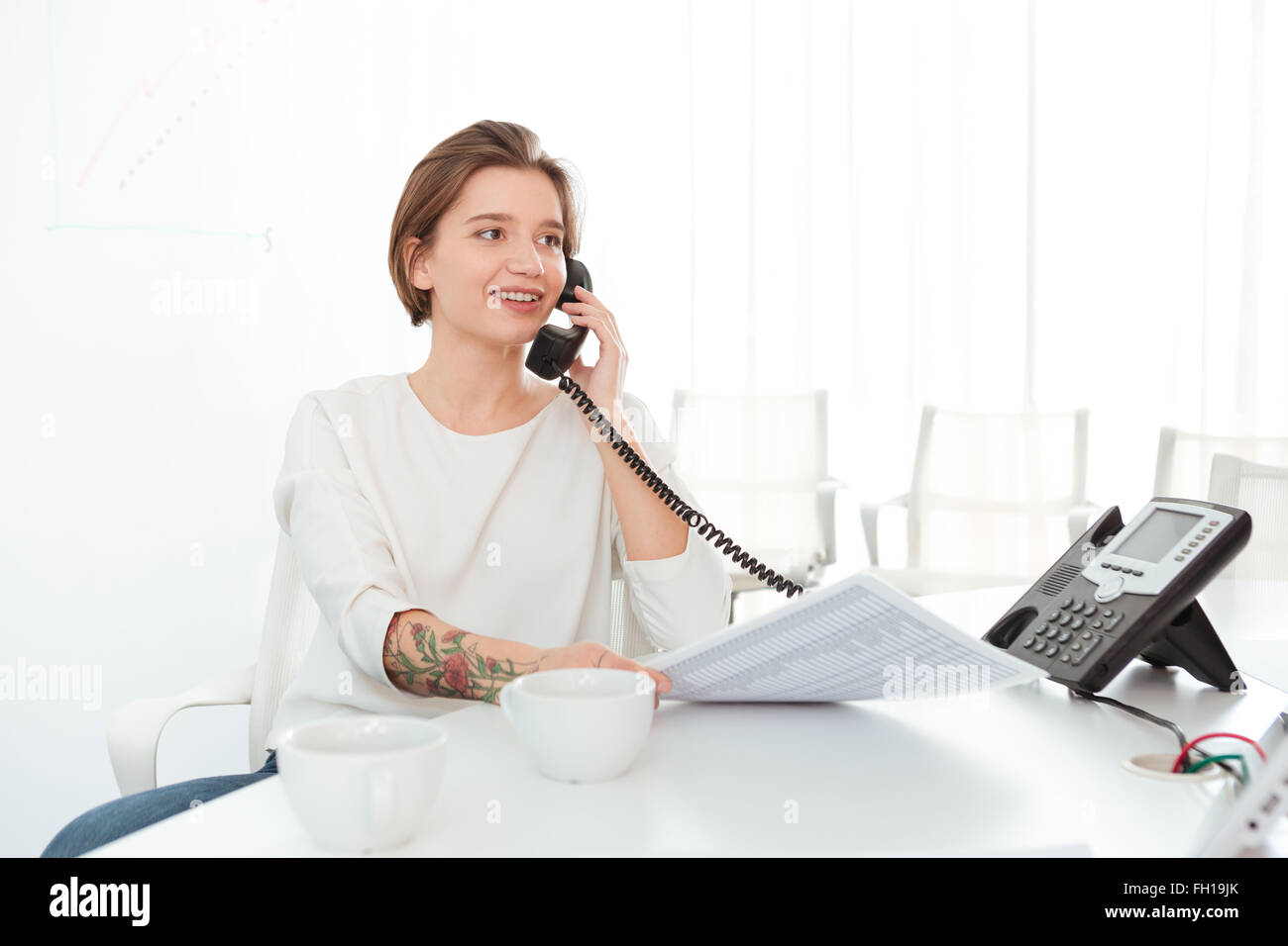 Smiling beautiful young woman sitting in office and talking on telephone - Stock Image