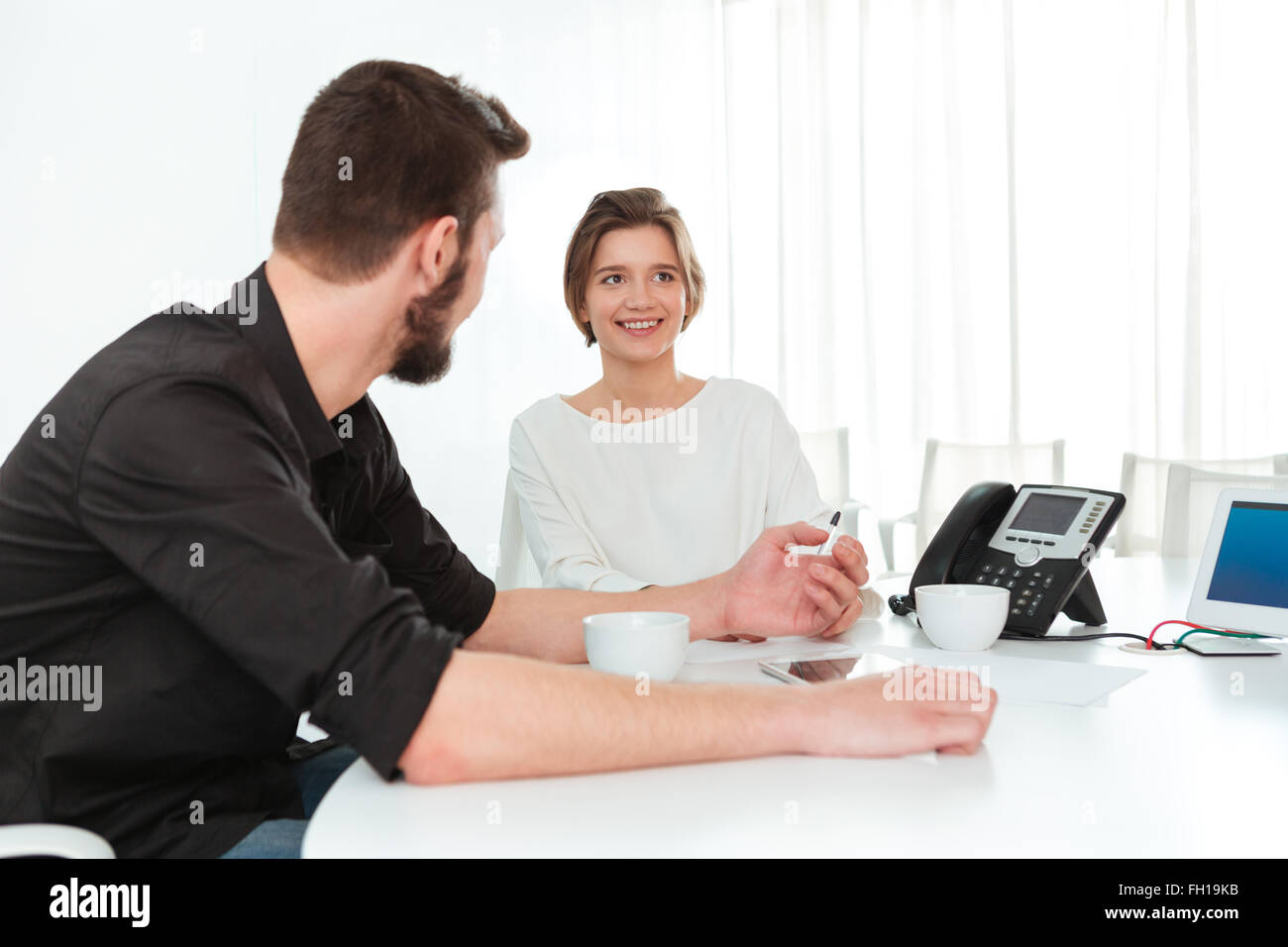 Two smiling young business people sitting and talking on the meeting in office - Stock Image